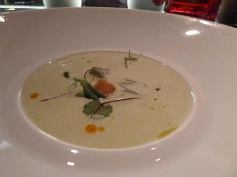 Green asparagus velouté served with goat cheese ravioli