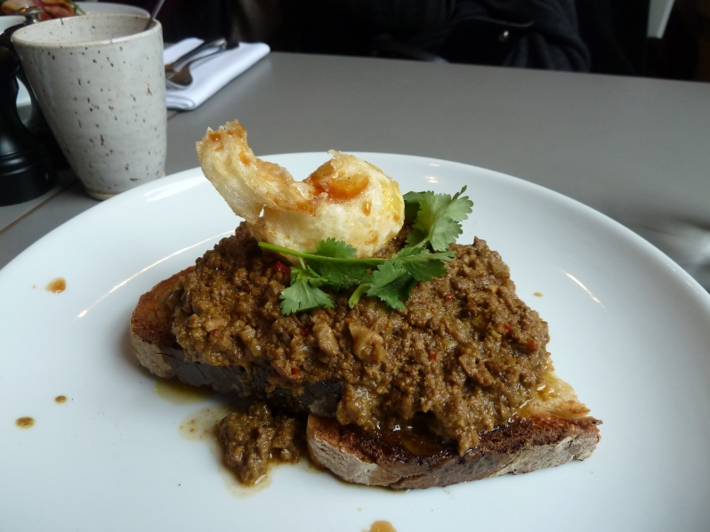 Rendang on toast with crispy quail's egg