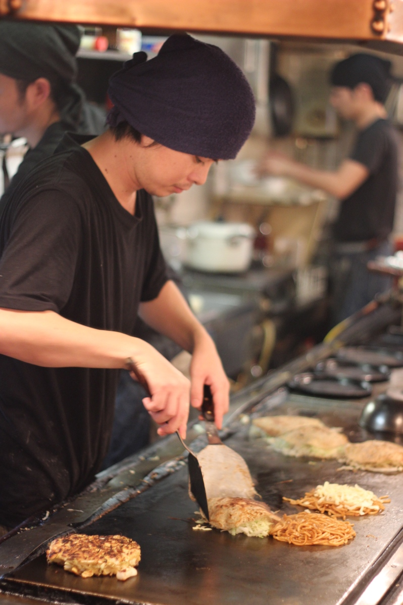 Okonomiyaki being fried on the griddle along the counter